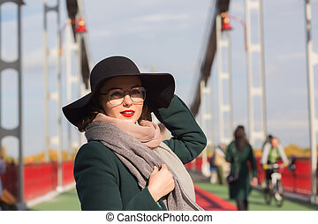 Lifestyle fashion portrait of romantic brunette model walking at the city, wearing trendy outfit