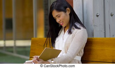 asian woman with notebook drinking coffee on bench -...