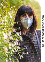 Lifestyle of a young brunette with mask next to beautiful daisies. First walks of the uncontrolled Covid-19 pandemic