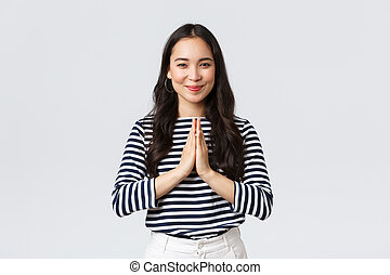 Lifestyle, people emotions and casual concept. Cute asian girl in casual outfit smiling as saying namaste, holding hands in pray, pleading or greeting guests with polite bow