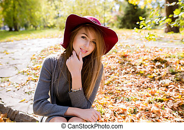 Lifestyle photo of fashionable young woman with natural makeup posing in red hat