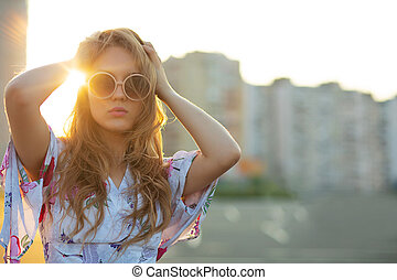 Lifestyle portrait of adorable blonde girl wearing sunglasses posing at the parking. Empty space