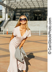 Lifestyle portrait of cheerful blonde girl in trendy dress holding grey jacket, walking at the city