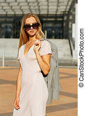 Lifestyle portrait of classy blonde girl in trendy dress holding grey jacket, walking at the city