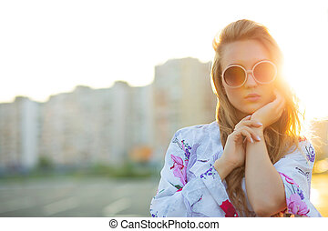 Lifestyle portrait of elegant blonde girl wearing sunglasses posing at the parking. Empty space
