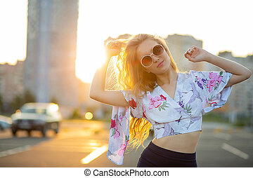 Lifestyle portrait of fashionable blonde woman wearing sunglasses posing at the parking. Empty space