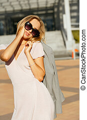 Lifestyle portrait of flirty blonde girl in trendy dress holding grey jacket, walking at the city