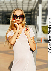 Lifestyle portrait of glamor blonde girl in trendy dress holding grey jacket, walking at the city