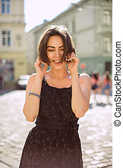 Lifestyle portrait of happy woman wearing trendy dress, walking on the city streets