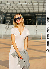 Lifestyle portrait of merry blonde girl in trendy dress holding grey jacket, walking at the city