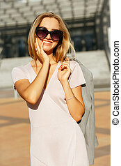Lifestyle portrait of positive blonde girl in trendy dress holding grey jacket, walking at the city