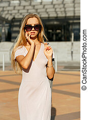 Lifestyle portrait of seductive blonde girl in trendy dress holding grey jacket, walking at the city