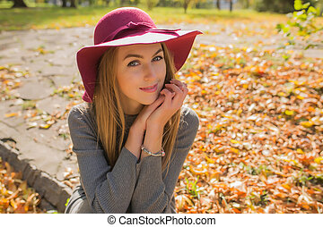 Lifestyle portrait of tender young woman with natural makeup posing in red hat. Empty space