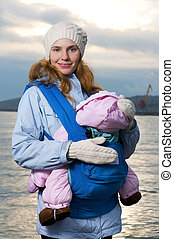 Lifestyle portrait of young mother and baby outdoor
