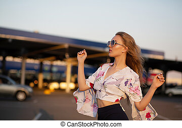 Lifestyle shot of glamor blonde woman wearing sunglasses posing at the parking. Empty space