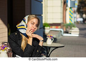 Lifestyle shot of stylish blonde model with natural makeup posing at the street cafe. Space for text