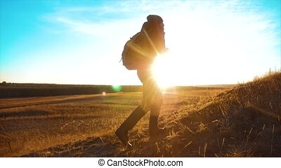 lifestyle Silhouette hiker man of backpacker. steadicam motion video sunlight sunset person side view walking toward successful. lonely man with sunset background. Travel and success concept the adventure