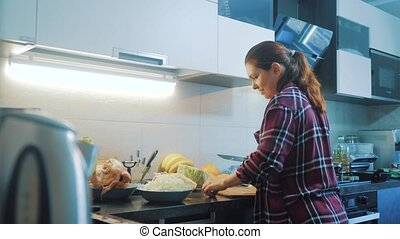 lifestyle woman in the kitchen preparing a meal concept. girl in the kitchen cuts cabbage with a knife. cook vegetarian food healthy food. girl at home in the kitchen slow motion video