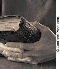 Lifetime of Faith - Old hands holding a worn Bible