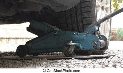 Lifting a car outdoors - Car mechanic lifting car rear wheel...