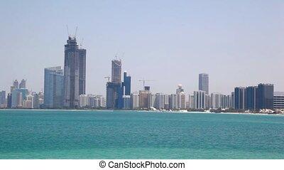 lifting cranes near building skyscrapers on coast of sea in Abu Dhabi, UAE
