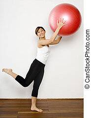 Lifting Fitness Ball - A young asian woman in sportswear...