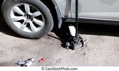 Lifting jack under car, few tools lie near, shown in motion