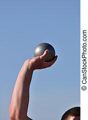 Lifting Shot Put - Man Lifting Shot Put at a Track and Field...