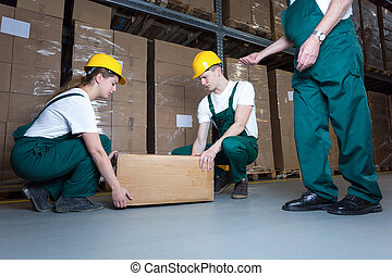 Lifting the box - Two young workers lifting heavy box in...