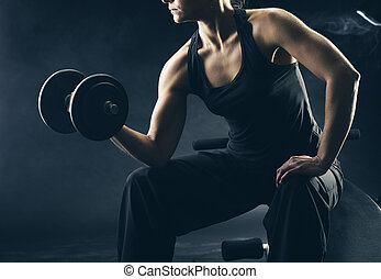 Lifting the dumbbells - Young woman lifting the dumbbells