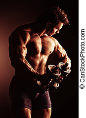 lifting weights - Portrait of a handsome bodybuilder posing...