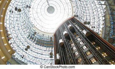 Lifts move downwards and upwards under glass calotte of tower