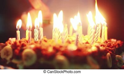 Lighing candles on a candle during birthday.