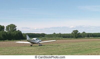 Light aircraft moving on field
