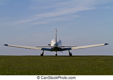 Light aircraft on a grass airfield pictured from behind at a...
