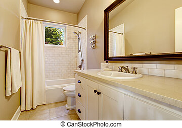 Light bathroom interior with white cabinet and shower with tile wall.