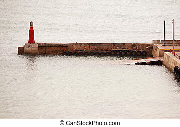 Red light beacon at harbour on breakwater