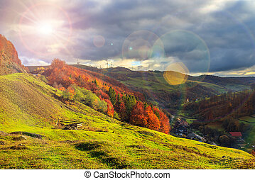 light beam falls on hillside with autumn forest in mountain...
