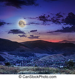 light beam falls on hillside with autumn village in mountain...