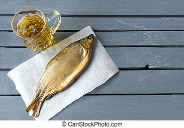 light beer mug, dried fish on grey wooden surface