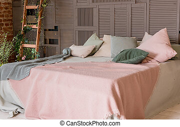 Light beige pink blanket on bed with green mint pillows. Stylish cozy scandinavian bedroom interior: bed, wooden ladder, wooden wall. loft apartment interior. Minimalist interior