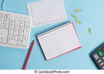 Light blue desk with empty paper notes, computer keyboard and office appliances. Blank space on reminders. Notebook papers and a chart in a square sheet with numbers.
