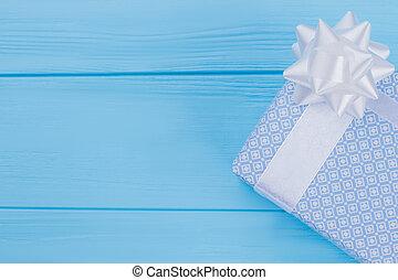 Light blue elegant gift box on wood.