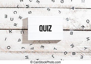 Light box with quiz text on white wooden background