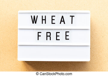 Light box with word wheat free on wood background
