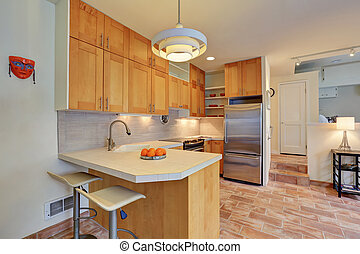 Light brown kitchen interior with steel appliances