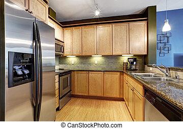 Light brown kitchen with hardwood floor and granite.