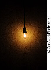 Light bulb - A small clear light bulb hanging next to a wall