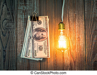 light bulb and dollar hang on wood background