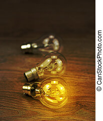 Light bulb glowing on a wooden background